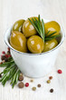 green olives in a metallic cup on wooden surface