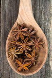 star anise in a spoon on wooden surface
