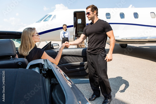 Bodyguard Helping Elegant Woman Stepping Out Of Car - 61882365