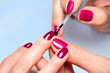 Woman applying nail varnish to finger nails - 61882594