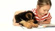 little girl with a puppy reading a book