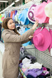 Woman looking for summer hats on shop shelf