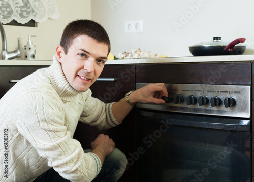 Man roasting meat in the oven