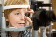 Optician's Hand Checking Boy's Eye With Lens