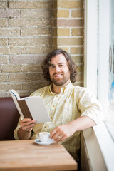 Man With Book And Coffee Cup Sitting In Cafeteria