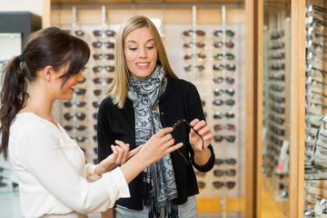 Woman Assisting Customer In Selecting Glasses