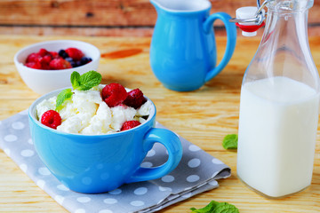 cottage cheese with berries and milk in a bottle