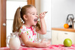 kid girl eating healthy food in kitchen