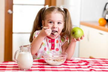 happy kid eating corn flakes with milk