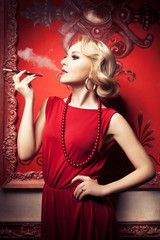 Sensual blonde smoking cigarette in red vintage room