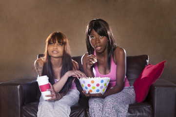 two young multi-racial girls watching a movie