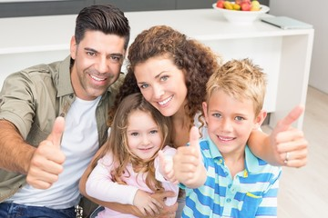 Happy parents giving thumbs up with their young children
