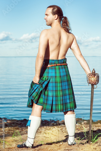 Scottish man with sword near the sea