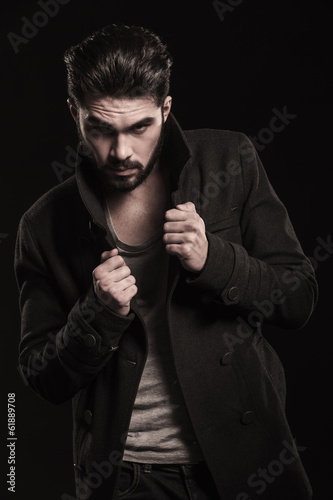 serious fashion model pulling his collar and poses