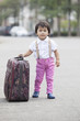 asian children walking on street with big suitcase use for journ