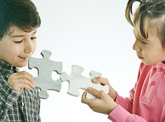 Kids connecting the jigsaw puzzle