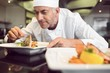 Concentrated male chef garnishing food in kitchen - 61892387
