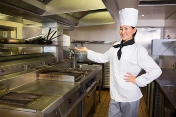 Confident female cook in kitchen