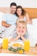 Smiling young family having breakfast in bed