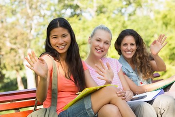 Female college friends sitting on campus bench