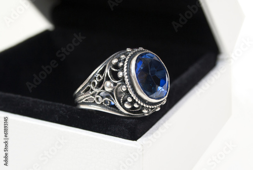 silver ring with a blue stone in a gift box