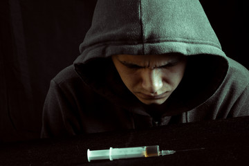 Grunge image of a depressed drug addict looking at a syringe