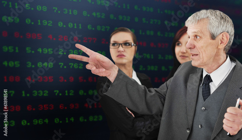 Successful group analyzing stock market on large digital display