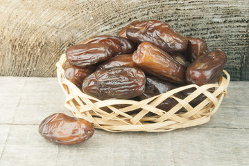 dried fruits from date palm in basket against wood
