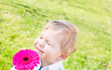 young boy with flower smiling