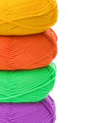 stack of yarn skeins in yellow, orange, green, purple colors on