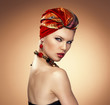 Fashion girl wrapped in red silk turban posing in studio