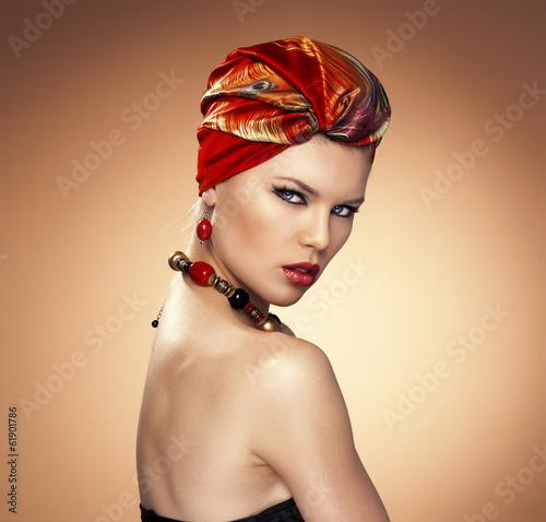 Fashion girl wrapped in red silk turban posing in studio