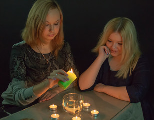 Two blondes conjure with candles