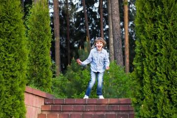 Little boy running on beautiful garden stairs
