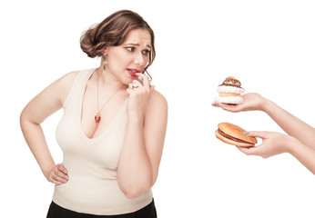 Plus size woman seduced with hamburger and pastry