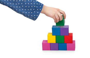 Child's hand building a brick tower isolated on white background