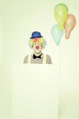 Lachender Clown mit Werbeschild