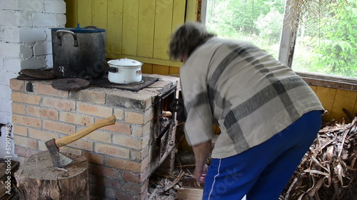 senior woman put firewood in rural kitchen stove food pot boil