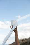 Woman hand holding a roll of toilet paper in the wind blue sky