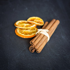Cinnamon sticks with orange, aromatic spices concept