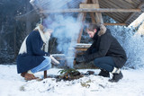 Young couple making fire in forest in winter