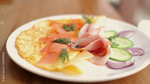 Plate with tasty breakfast, omelette, vegetables, salmon