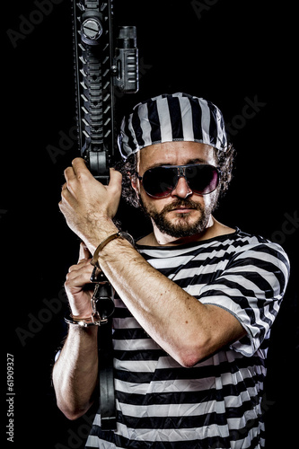 Security.Prison riot concept. Man holding a machine gun, prisone