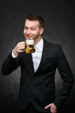 happy man in black suit holding beer mug