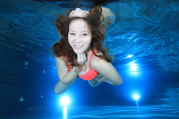 Woman smiling underwater in the pool