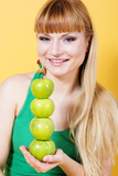 Happy blonde girl with green apples