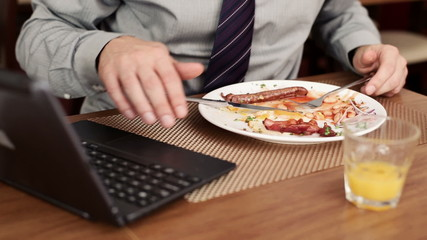 Businessman typing on laptop and eating tasty english breakfast