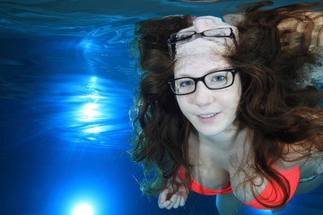 Woman underwater in the pool with glasses