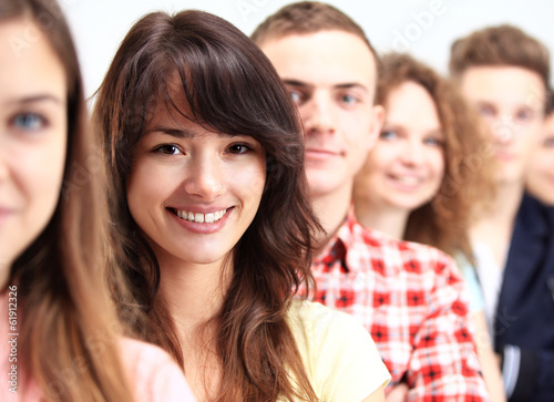 Young woman standing in front of young people standing in a row