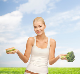 smiling woman with broccoli and hamburger